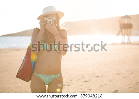 Attractive fit trendy modern hipster woman taking photos with retro vintage film camera.Lifestyle photographer.Summer beach woman taking picture during summer holiday vacation travel.Sexy cool hipster - stock photo
