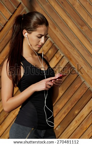 Attractive fit woman in sportswear listening to music with her headphones while training outdoors at beautiful sunny day, young female runner selecting music on cell phone while getting ready for run - stock photo