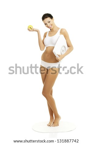 Attractive fit woman with scale and apple, isolated on white - stock photo