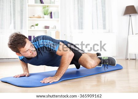 Attractive Fit Young Man Planking on an Exercise Mat While Lifting One Leg and Looking to the Right.
