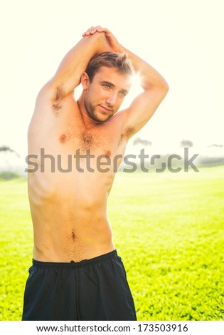 Attractive fit young man stretching before exercise workout, sunrise early morning backlit. Healthy lifestyle sports fitness concept. - stock photo