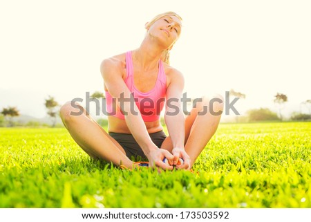 Attractive fit young woman stretching before exercise, sunrise early morning backlit. Healthy lifestyle sports fitness concept. - stock photo