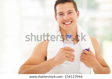 attractive fitness man drinking water after working out