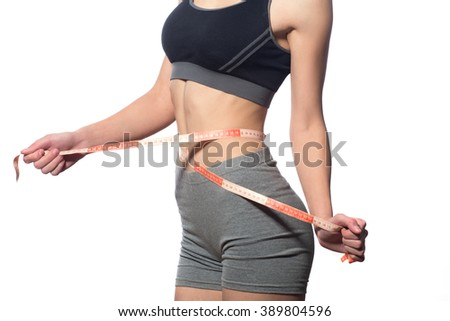 attractive fitness model with measuring tape on a white background - stock photo