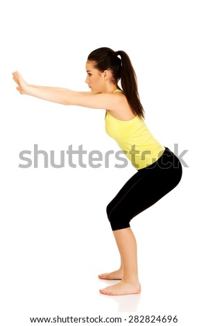 Attractive fitness woman performs squats. - stock photo