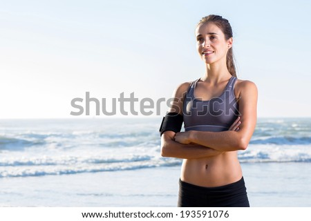 attractive fitness woman with arms crossed on beach