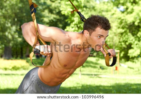 Attractive fittness man doing exercises in park - stock photo