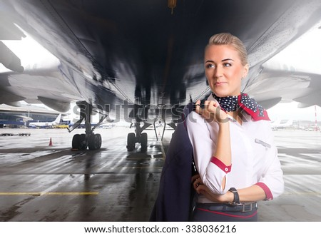 Attractive flight attendant near airplane in airport. - stock photo