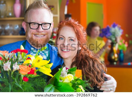 Attractive flower shop owners standing closely to each other in front of bouquet - stock photo