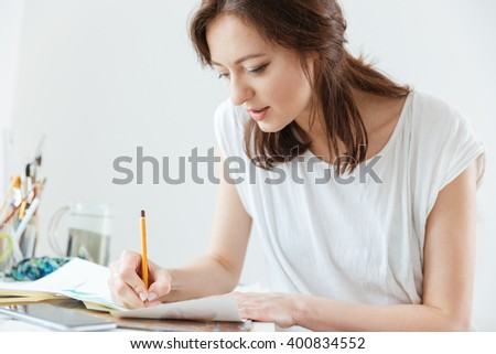 Attractive focused woman artist making sketches in workshop - stock photo