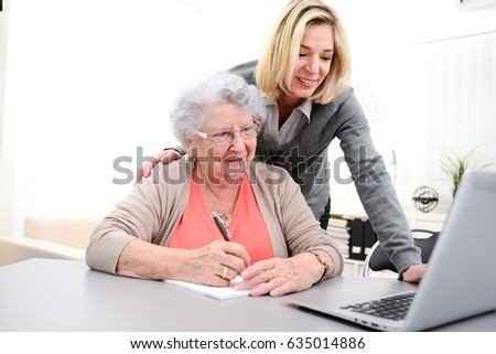 attractive forty years old woman helping with computer her mother for internet search , eighty years old senior woman at home