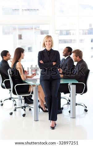 Attractive friendly businesswoman smiling at the camera in a meeting