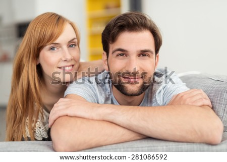 Attractive friendly couple relaxing at home resting on the edge of the sofa looking at the camera with warm smiles - stock photo