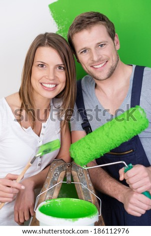 Attractive friendly young couple redecorating the house standing on either side of a stepladder holding a paint roller and brush and a tub of green paint - stock photo