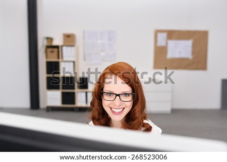 Attractive friendly young redhead businesswoman with a beaming smile wearing glasses looking over the top of desktop computer at the camera - stock photo