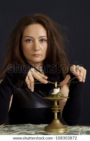 Attractive girl as a witch on a dark background - stock photo