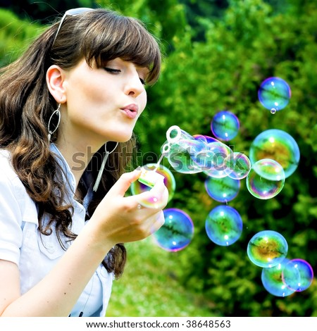 attractive girl blowing soap bubbles in summer green park