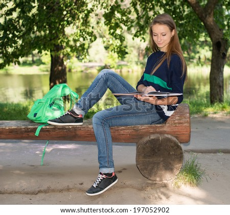 Attractive girl college student reading a book on bench in the park. - stock photo