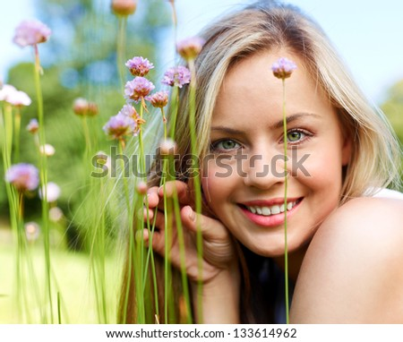 Attractive girl dreaming in a grass with flowers (medium format image) - stock photo