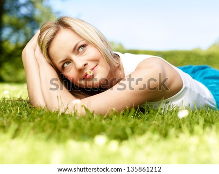 Attractive girl dreaming in a grass with flowers (medium format image)
