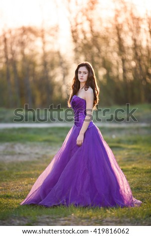 Attractive girl dressed evening gown at sunset