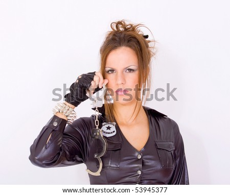 Attractive girl dressed in police uniform holding a handcuffs - stock photo