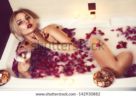 Attractive girl enjoys a bath with milk and rose petals - stock photo
