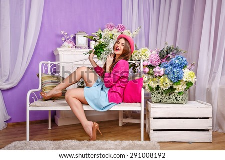 Attractive girl holding a bouquet of lilies of the valley and laughs. The girl sitting on a bench. The concept of innocent beauty. - stock photo