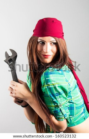attractive girl holding adjustable wrench - stock photo