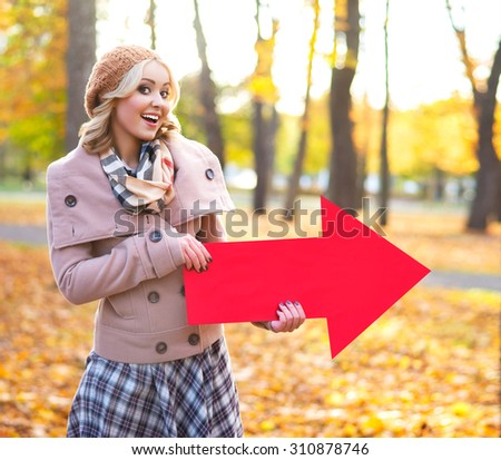 Attractive girl holding an arrow banner in the park. - stock photo