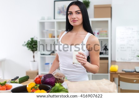 Attractive girl holding glass of milk, having healthy snack while preparing vegetable dish. Beautiful fit female cooking home. - stock photo