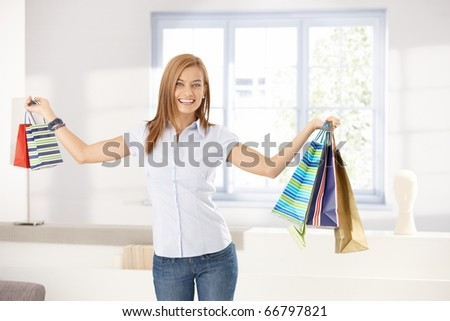 Attractive girl holding shopping bags in hands, smiling happily at home.?
