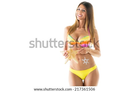 Attractive girl in a bikini holding a starfish. Isolated on white background. - stock photo