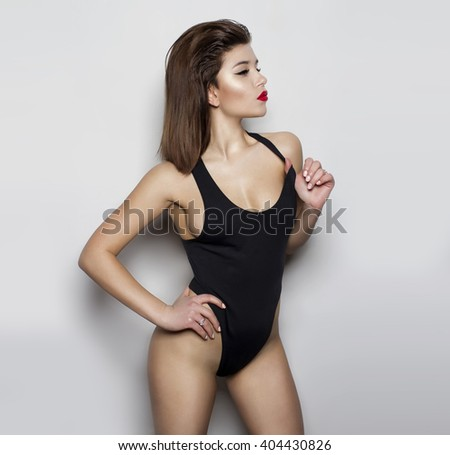 attractive girl in a black bathing suit on a grey background with a perfect body and a radiant  beautiful smile by putting his hands in the side for magazine cover - stock photo