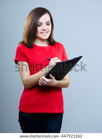 attractive girl in a T-shirt and jeans holding a folder in one hand and in the other a pen and wrote something on a gray background