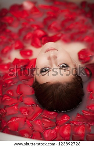Attractive girl in bath with milk and rose petals. Spa treatments for skin rejuvenation. Alluring woman with bright makeup in Spa salon. Pretty sexy brunet relaxing in jacuzzi with red flower petals - stock photo