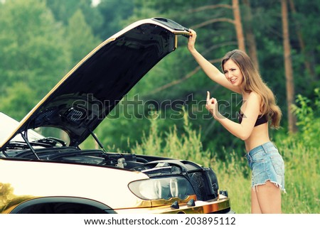 attractive girl in bikini looking under the hood of a car - stock photo