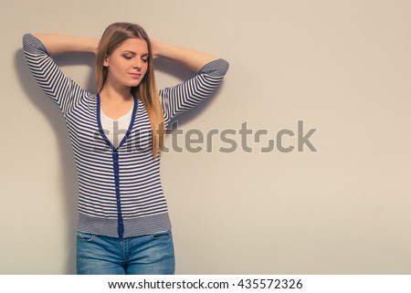Attractive girl in casual clothes is looking away and smiling while standing with hands behind head against gray background - stock photo