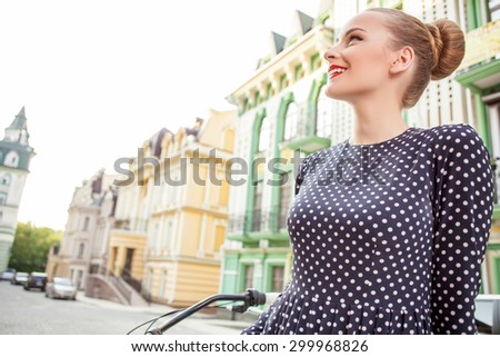 Attractive girl in retro style is sightseeing in city. She is leaning on her bicycle and relaxing. The girl is looking aside and smiling with joy. Copy space in left side - stock photo