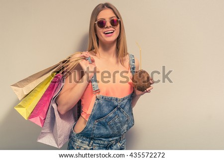 Attractive girl in summer clothes and sun glasses is drinking a coconut milk, holding shopping bags and smiling, against gray background - stock photo