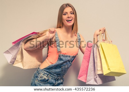 Attractive girl in summer clothes is holding shopping bags, looking at camera and smiling, against gray background - stock photo