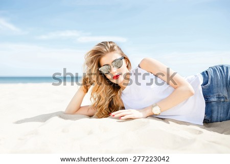 Attractive girl in sunglasses posing lying on the sea beach on a sunny day on the background of the sea and clear sky. - stock photo