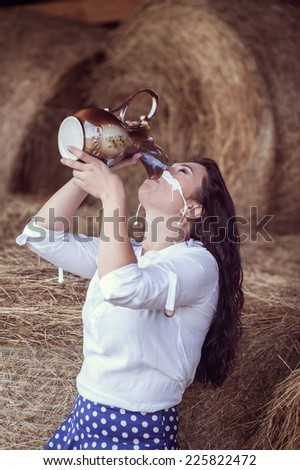 Attractive girl in the hay drinking milk - stock photo