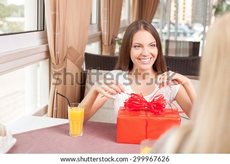 Attractive girl is receiving a gift from her female friend. She is opening it with pleasure and smiling. The ladies are sitting opposite each other. Copy space in left side - stock photo