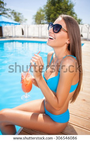 Attractive girl is sitting near a swimming pool and relaxing. She is deinking a cocktail and smiling - stock photo