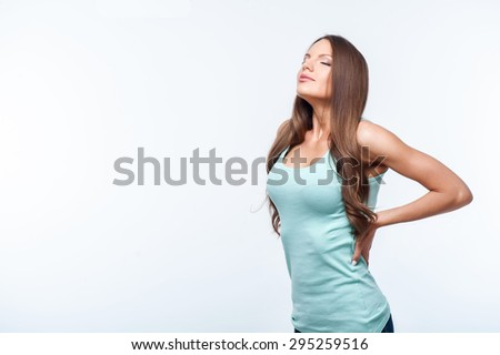 Attractive girl is standing with arms akimbo. She is resting and closing her eyes with pleasure. Isolated on background and copy space in left side - stock photo