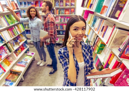 Attractive girl is talking on the mobile phone and looking at camera while choosing book at the bookshop, young man and girl in the background - stock photo