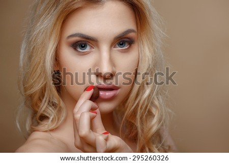 Attractive girl is touching chocolate candy to her lips. She is looking forward with temptation. Isolated on brown background and there is copy space in right side - stock photo