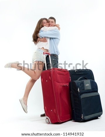 Attractive girl jumping in her boyfriend arms surrounded by baggage