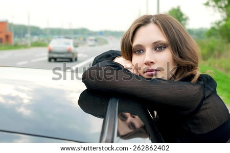 Attractive girl leaning against a car outdoors - stock photo